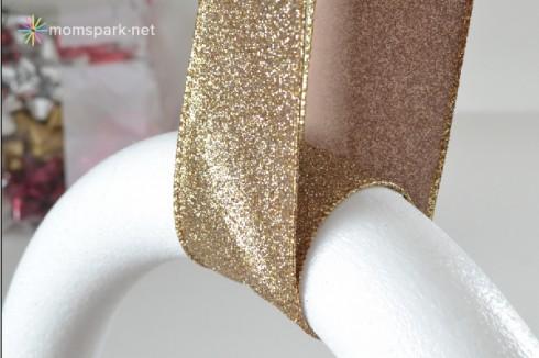 Nguyên liệu: form hình vòng hoa, ruy băng, khoảng 100 nơ gói quà đủ kích cỡ, keo nóng. Bước 1: cố định ruy băng quanh form vòng hoa bằng keo nóng.