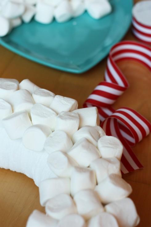 Bước 4: đính kẹo Marshmallow lên khắp bề mặt form, trừ phần tiếp xúc với tường khi treo vòng hoa lên.