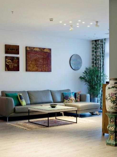 Một góc phòng khách với sự cân đối trong bài trí giữa nhóm tranh sơn mài của họa sĩ Phi-Phi Oanh và họa sĩ Vũ Đức Trung với bộ sofa có thiết kế hiện đại của BoConcept.