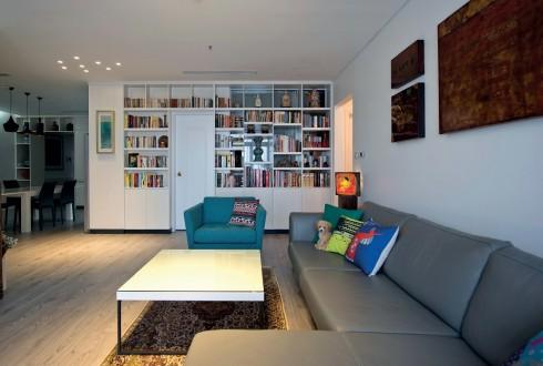 Căn phòng không cửa sổ đã được thiết kế lại, lấy sáng tự nhiên bằng một kệ sách lớn.