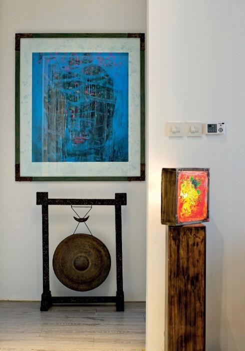 """Việc phối hợp trưng bày đa chất liệu các nghệ phẩm cho ngôi nhà là một đầu tư lớn về công sức và gu thẩm mỹ (tác phẩm: """"Màu Xanh Yên Tĩnh"""" của họa sĩ Hà Mạnh Thắng, 2005 và hộp đèn của họa sĩ Đỗ Tuấn Anh)."""