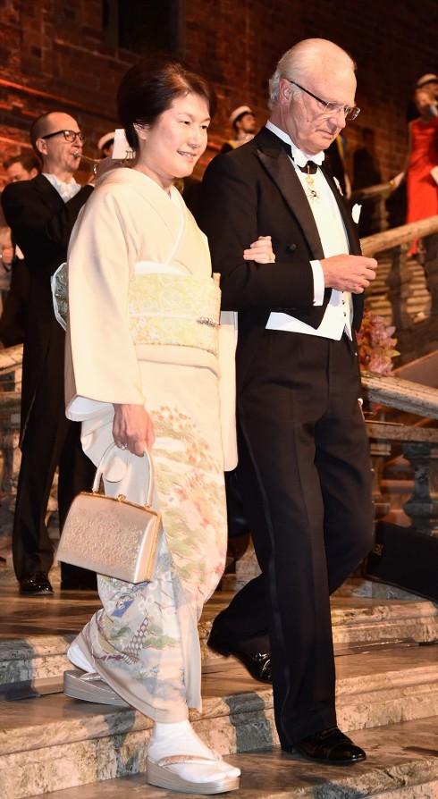 Bà Mitchiki Kajita, vợ của ông Taakaki Kajita được hộ tống bởi đức vua Thụy Điển King Carl XVI Gustaf. Bà Kajita mặc một chiếc áo kimono truyền thống bằng lụa