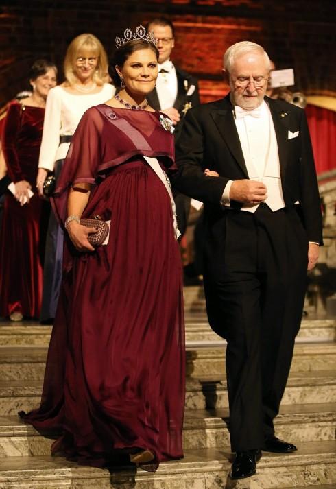 Công chúa Thụy Điển Victoria dù đang mang thai nhưng vẫn rất thanh tao trong chiếc váy màu đỏ, bộ trang phục càng hoàn hảo hơn với chiếc vương miện Connaught làm từ kim cương. Công chúa Victoria được hộ tống bởi nhà nghiên cứu Arthur McDonalds, một trong những học giả đạt giải Nobel hóa học 2015