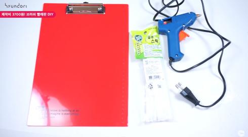 Bước 1: Chuẩn bị dụng cụ cần thiết: 1 tấm bảng mica (loại dùng để kẹp giấy), 1 cây súng bắn keo, 3-4 thanh keo.