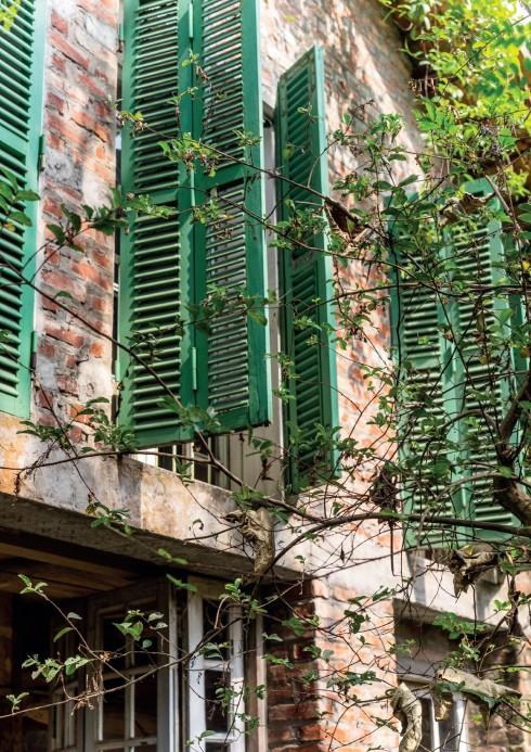 Các ô cửa kính cũ được ghép vào căn nhà sàn thô sơ, thoạt trông đây có vẻ như là một căn biệt thự hiền từ đâu đó ở Pháp