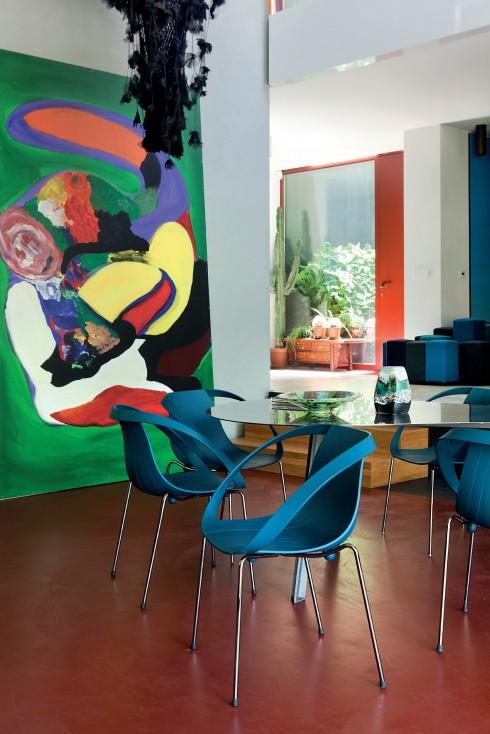 Nội thất với những màu sắc nổi bật mang đến nhịp điệu cho ngôi nhà, từ nền nhà màu đỏ cho đến sự tương ứng giữa ghế và tranh.