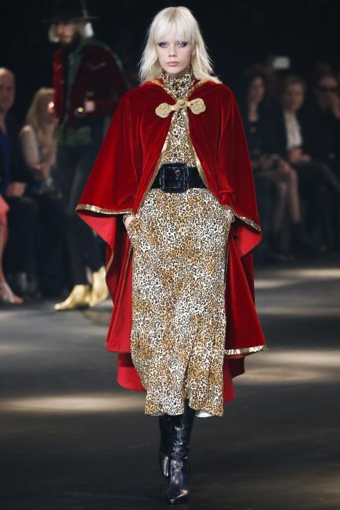 Váy lụa hoạ tiết da báo được phủ bên ngoài bởi chiếc áo cape nhung đỏ rực. Chất liệu nhung cũng được Hedi sử dụng phổ biến trong BST này.