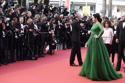 Nhân viên điều phối thảm đỏ Cannes đang tạm dừng khách mời phía sau để các nhiếp ảnh chụp hình nữ diễn viên.