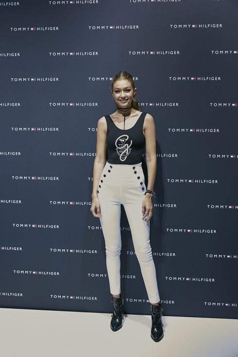 Gigi Hadid mặc thiết kế nằm trong BST TommyxGigi Quần super-skinny cạp cao màu trắng ,áo thun ôm Bodysuit màu đen, đôi giày boots phong cách thủy thủ.