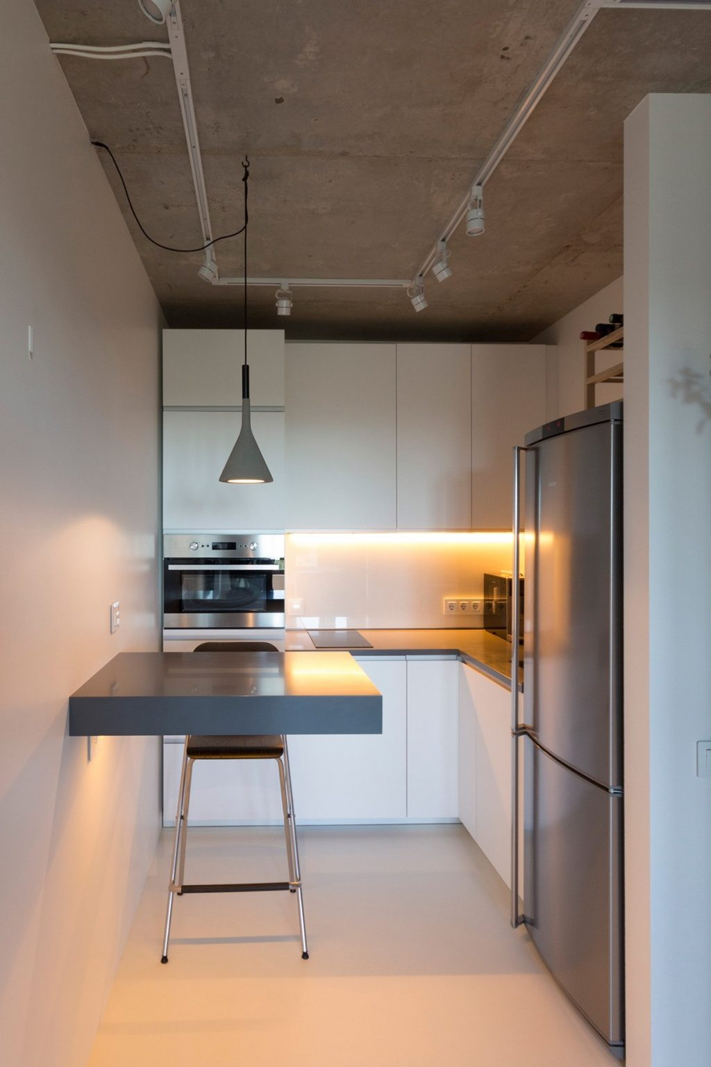 30.Minimalist-kitchen-white-walls-industrial-ceiling-grey-hanging-light-and-ledge-table