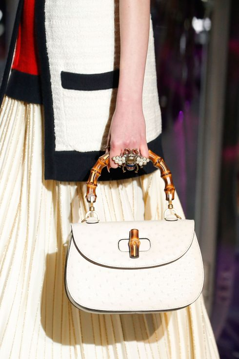 Chiếc túi với phần quai tre nổi tiếng của Gucci trên nền da đà điểu trắng và chiếc nhẫn bọ cánh cứng của Gucci.