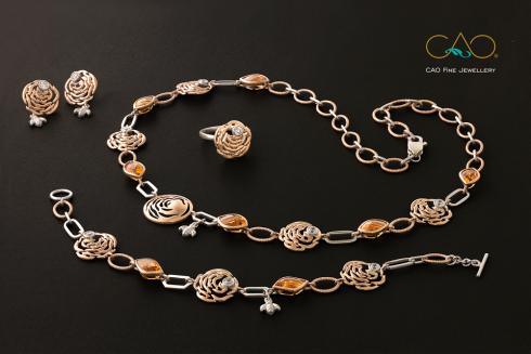 Bộ trang sức Glamorosa Beeroses là những đóa hồng cách điệu trên chất liệu vàng trắng kết hợp vàng hồng, đính đá Citrine màu vàng mật cùng những chú ong xinh xắn. Đây là thiết kế phù hợp sử dụng hàng ngày dành cho các bạn gái thời trang và phong cách.