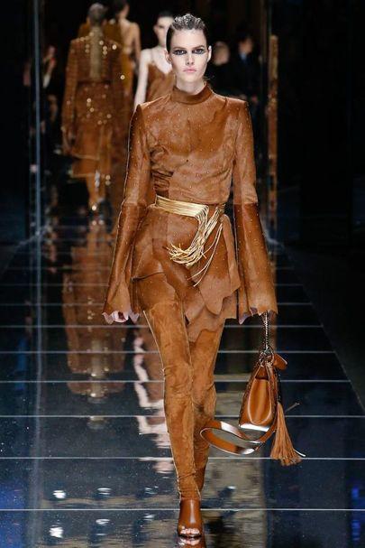 Chiếc thắt lưng vàng tạo điểm nhấn cho bộ trang phục da lộn độc đáo