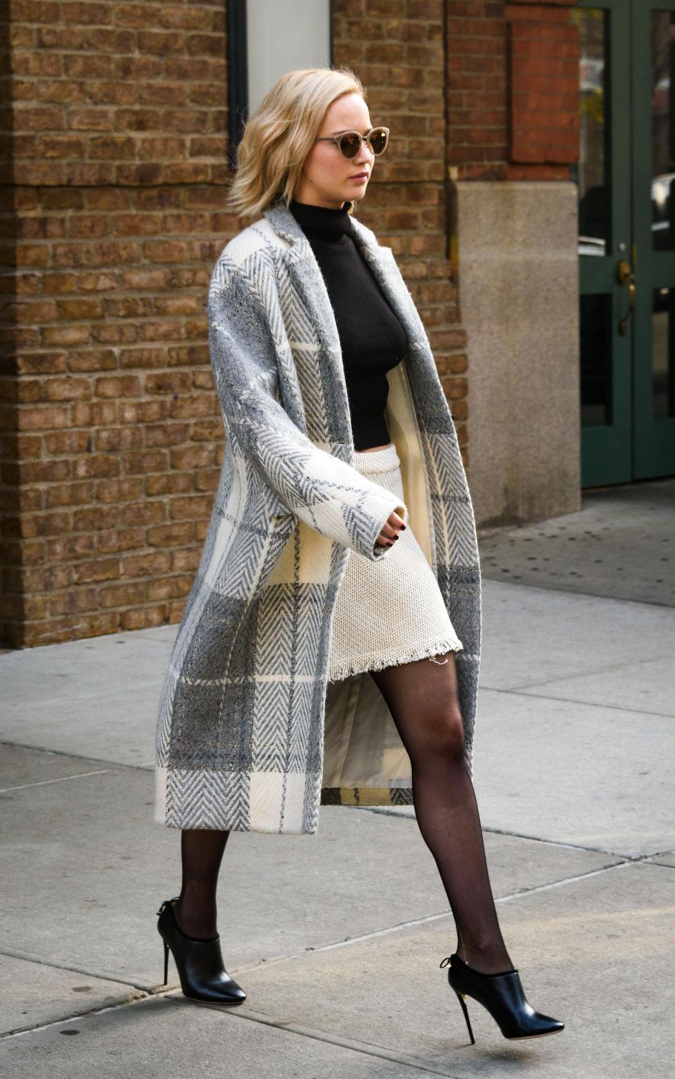 Jennifer trên đường đến tham dự buổi họp báo phim Joy. Bộ trang phục mix tông trắng đen từ chiếc kính râm, áo cổ cao, váy len tới đôi ankle boot. Chiếc áo dạ sọc caro chính là điểm nhấn làm dịu đi bộ trang phục chất lừ