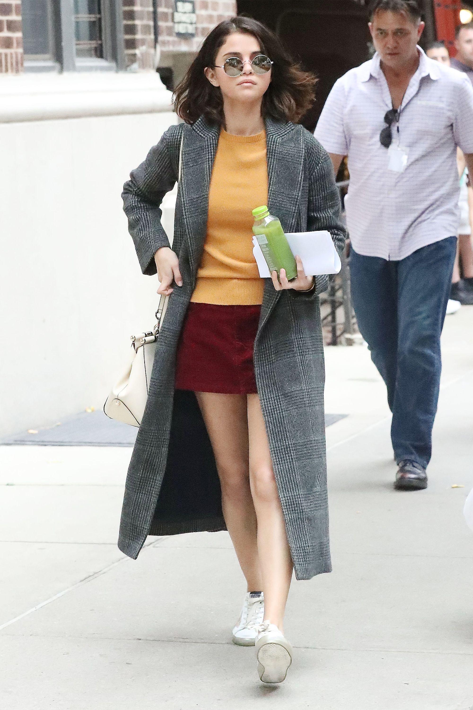 selena gomez mặc đẹp với giày tennis trắng và trench coat