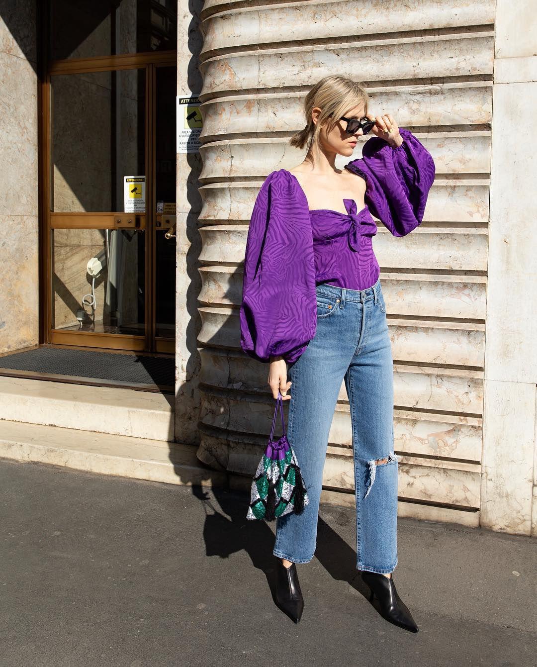 fashionista diện áo blouse tông màu tím cùng quần jeans, bốt cổ thấp và túi xách cùng tông