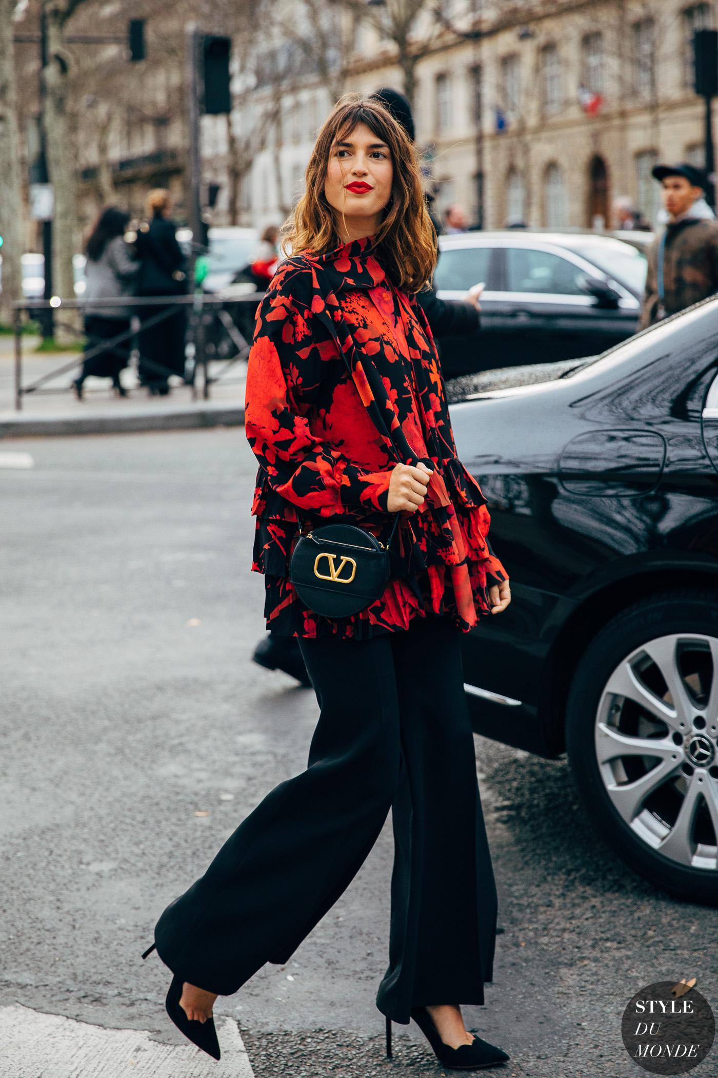 Jeanne Damas diện áo blouse họa tiết hoa đỏ cùng quần cullote đen, giày cao gót và túi xách hình học cùng tông
