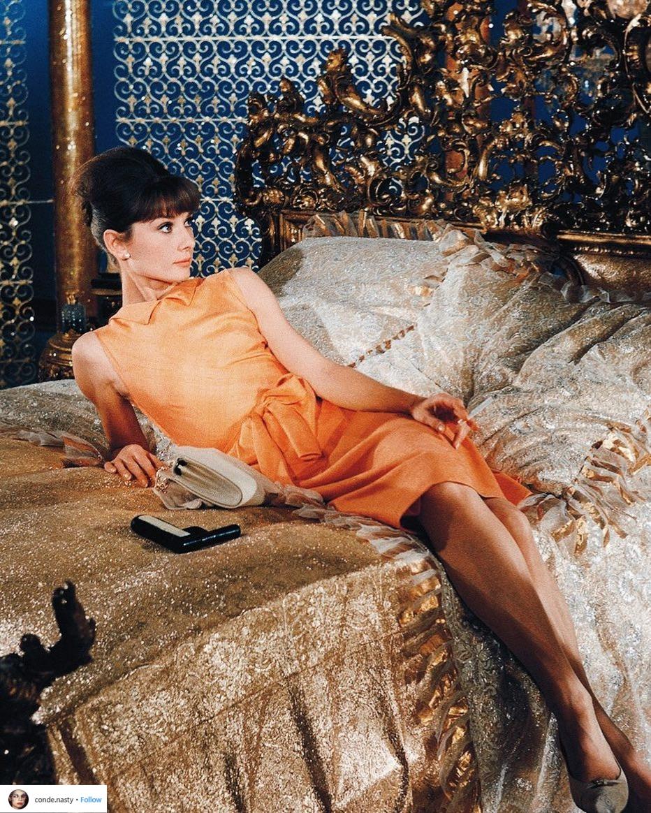 tài khoản Instagram thời trang conde.nasty đăng tải ảnh của Audrey Hepburn trong bộ đầm mini màu cam và kiểu tóc búi cao