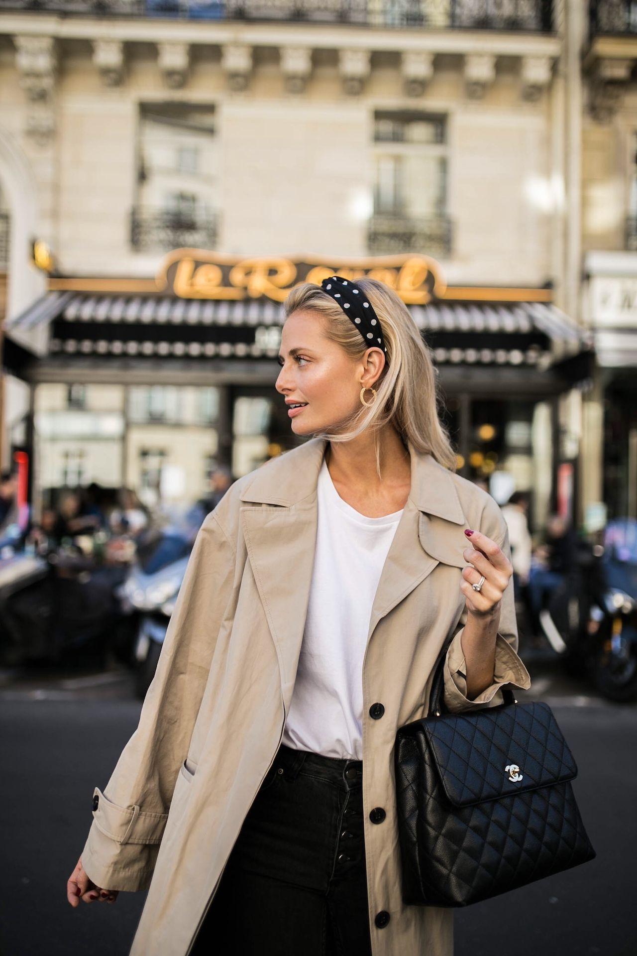 fashionista kết hợp phụ kiện băng đô nữ tính chấm bi đen trắng cùng trench coat màu beige, áo phông trắng, chân váy jeans đen và túi xách chanel đen