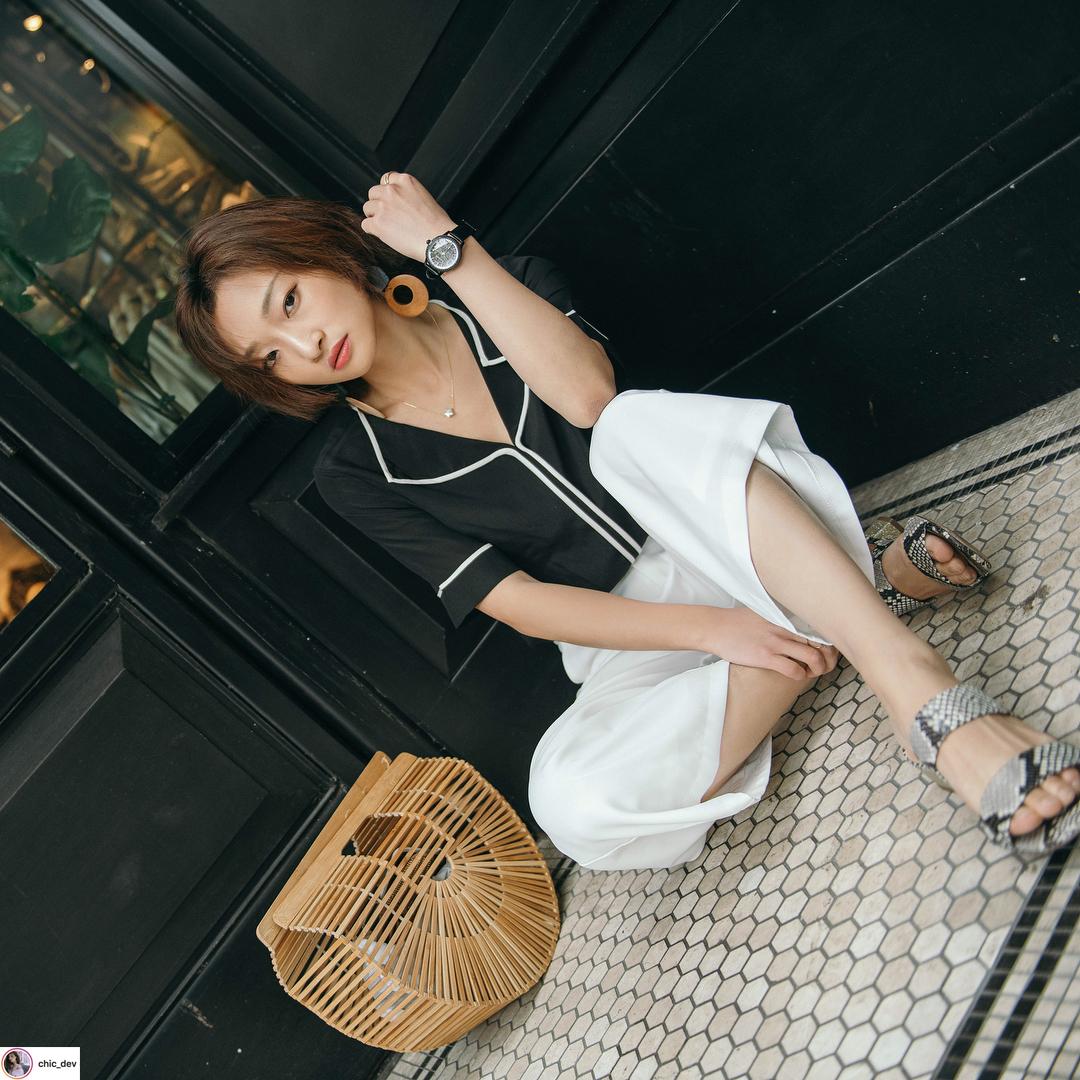 cô gái mặc đồ trắng đen và túi xách thủ công hình bán nguyệt