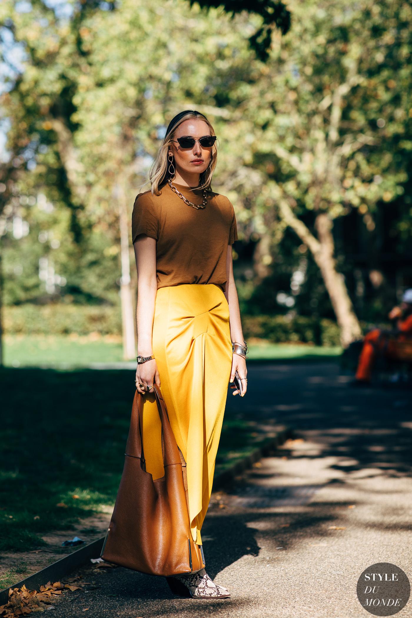 fashionista diện áo phông nâu đất, chân váy vàng, túi xách nâu đất, kính mát đen và băng đô đen tại tuần lễ thời trang london xuân - hè 2019