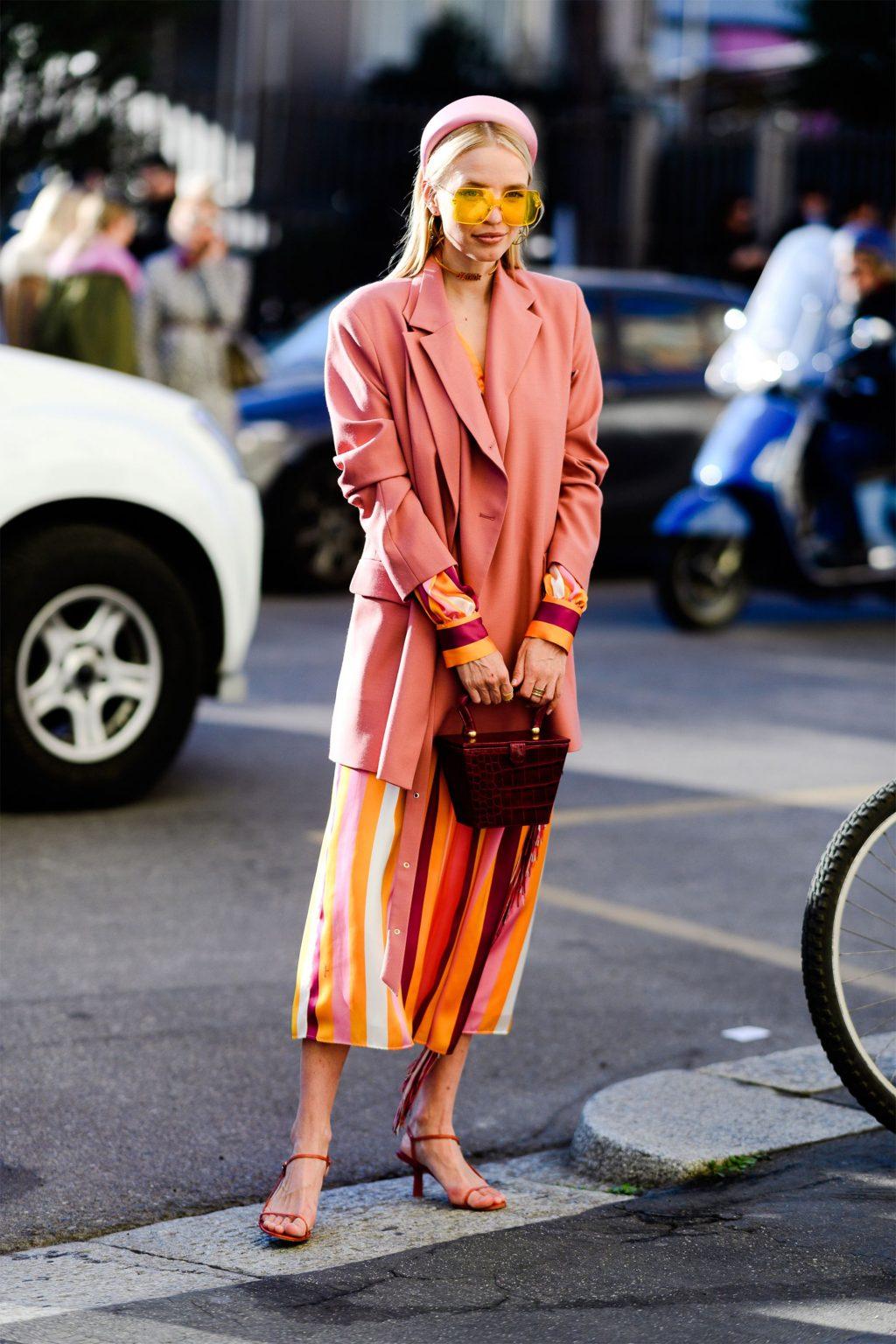fashionista diện blazer hồng, băng đô hồng, kính mát bản lớn vàng, đầm kẻ sọc và túi xách hình học