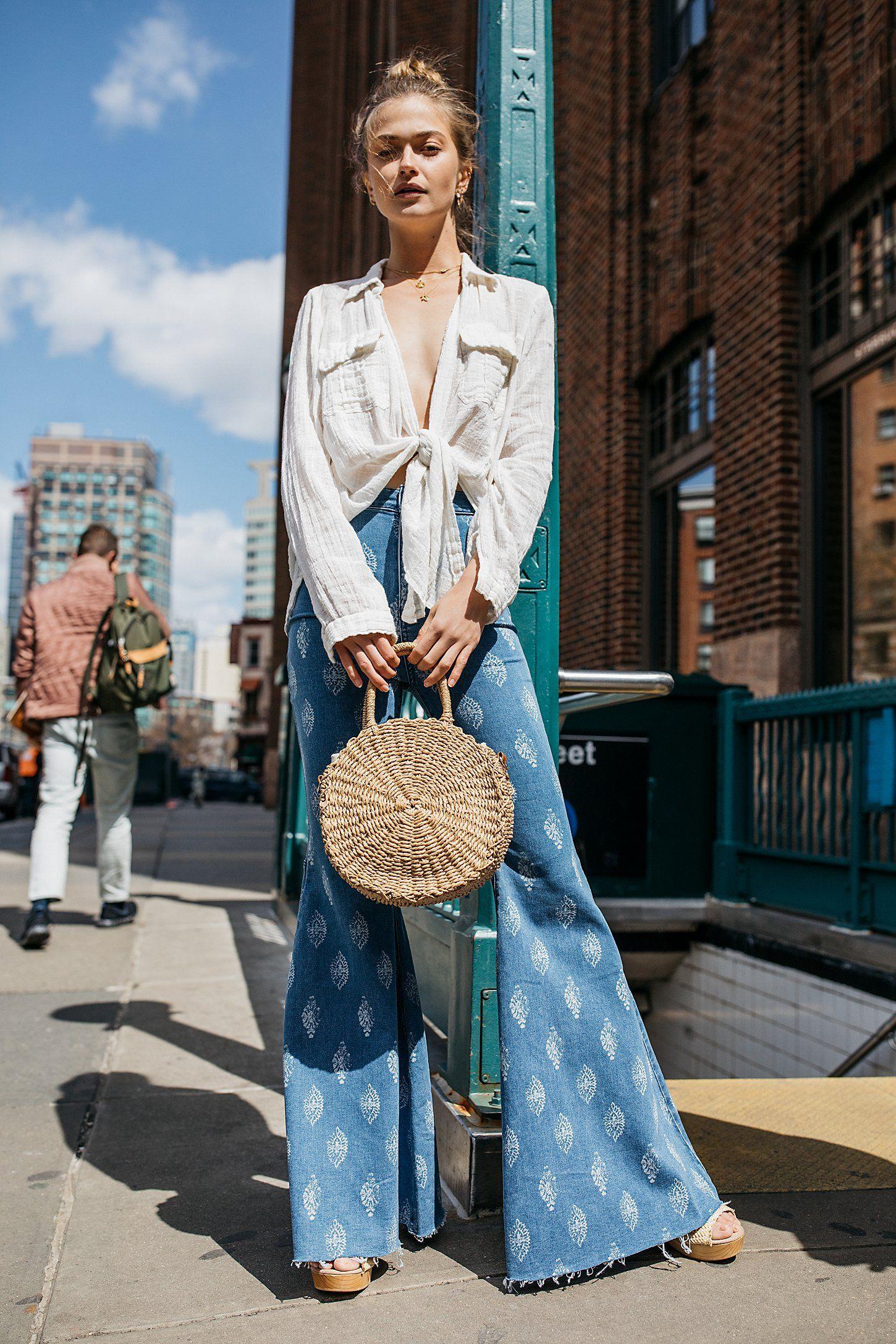 áo sơmi trắng buột vạt và quần jeans ống loe xanh