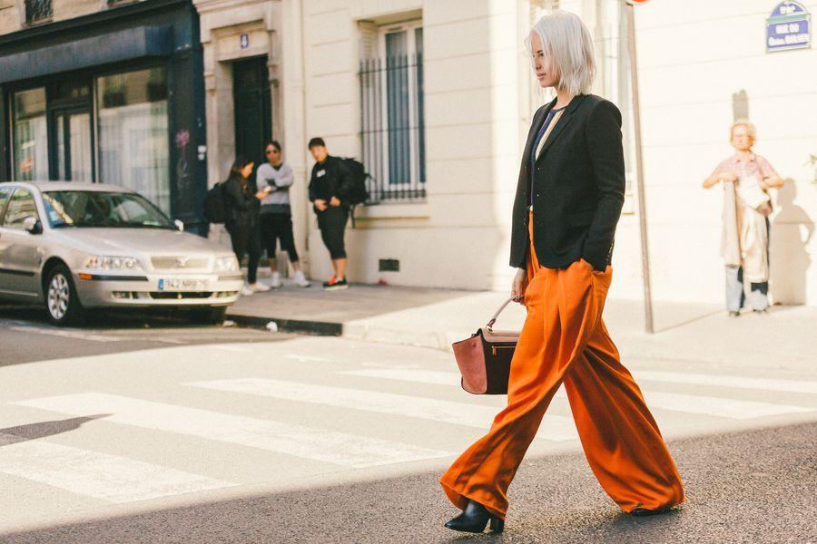 quần màu cam và áo vest đen