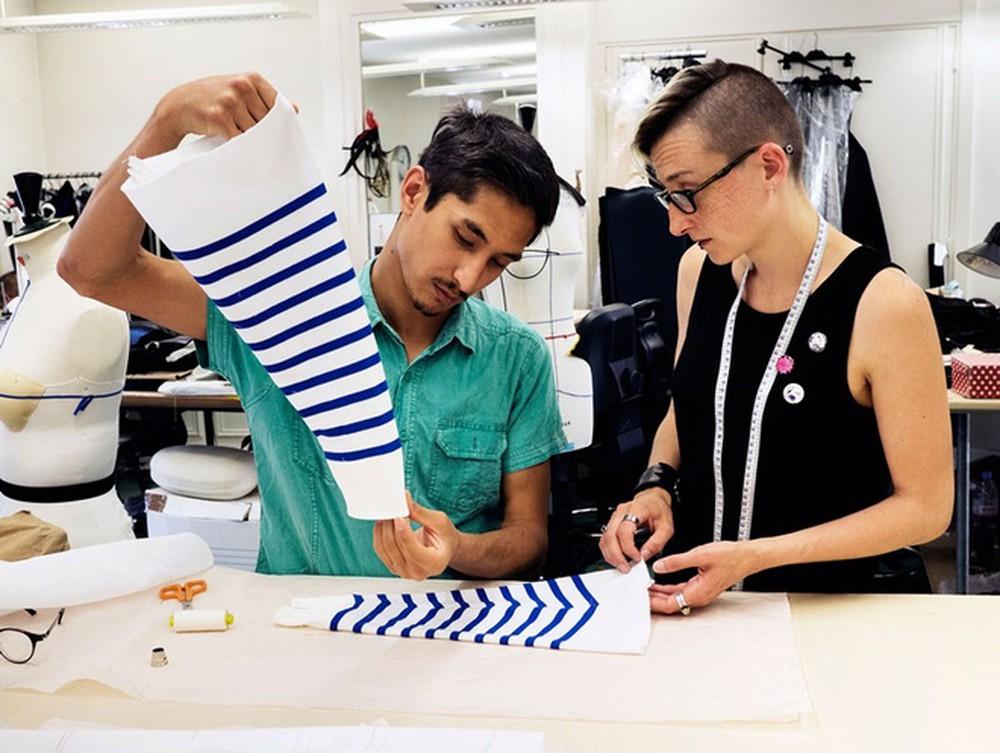 hai thợ may đang chỉnh tay áo của một thiết kế haute couture