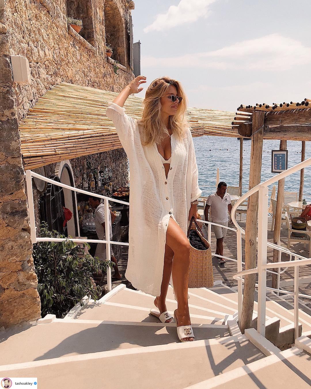 cô gái mặc đồ bơi và áo khoác dáng dài màu trắng