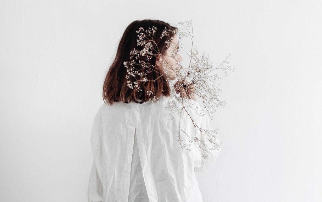 cô gái cầm bó hoa trắng