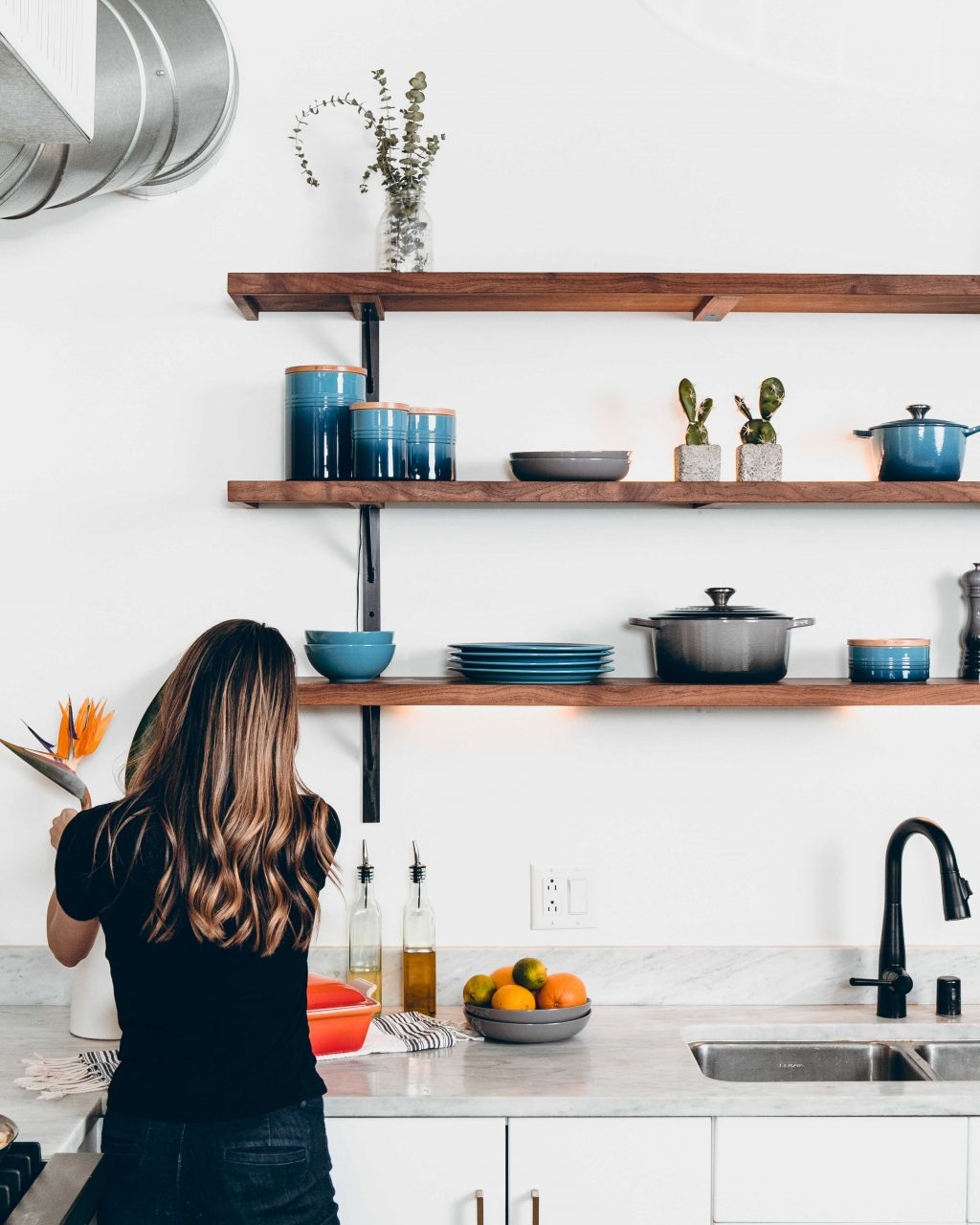 cô gái cắm hoa trong căn bếp tối giản