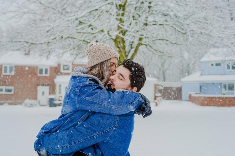 cặp đôi ôm nhau dưới tuyết