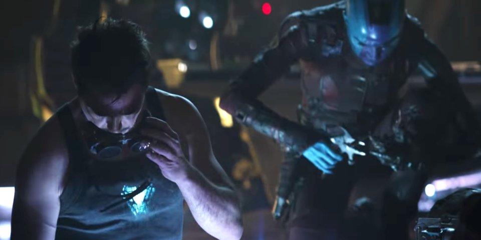 người đàn ông cầm chiếc kính bên cạnh người máy