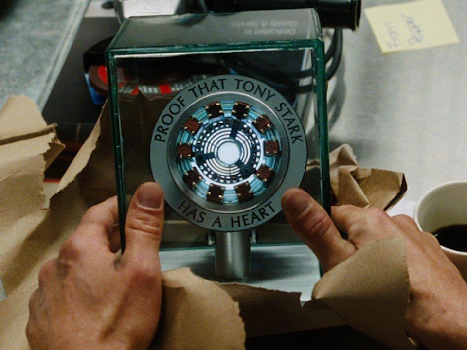 đôi tay cầm một bộ máy hình tròn màu xanh