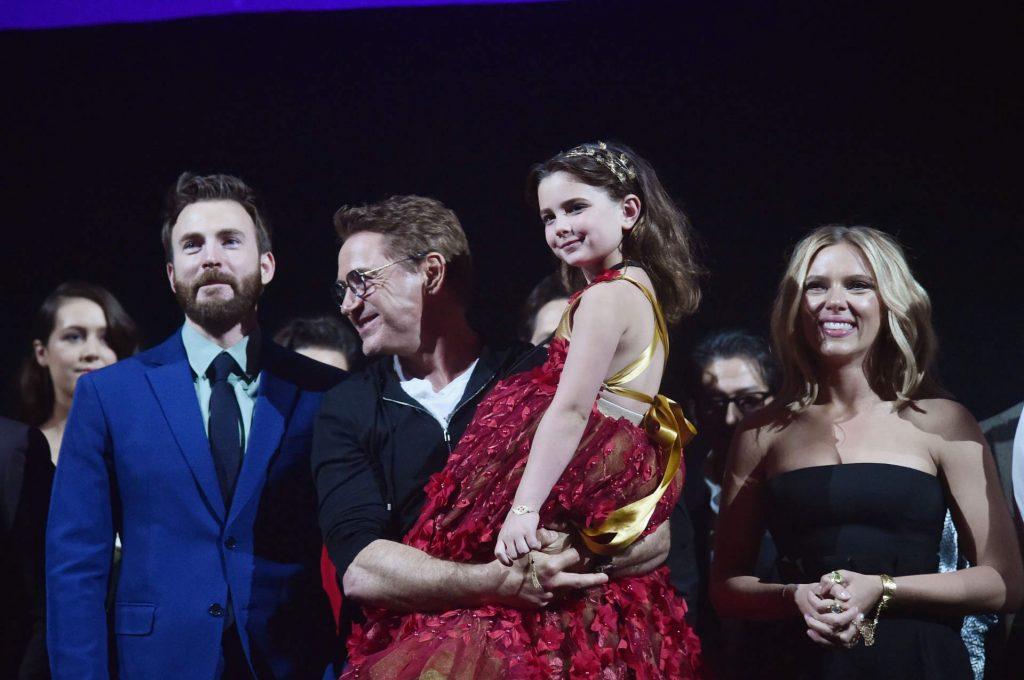 người đàn ông mặc suit xanh đứng cạnh người đàn ông bế bé gái mặc váy đỏ và đứng cạnh một người phụ nữ tóc vàng