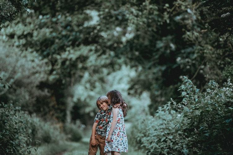Bé gái hôn má bé trai trong vườn cây