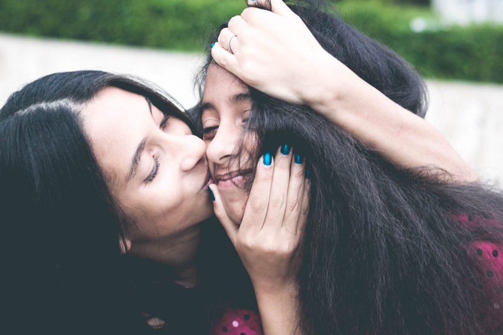 Hai cô gái tóc đen dài hôn má
