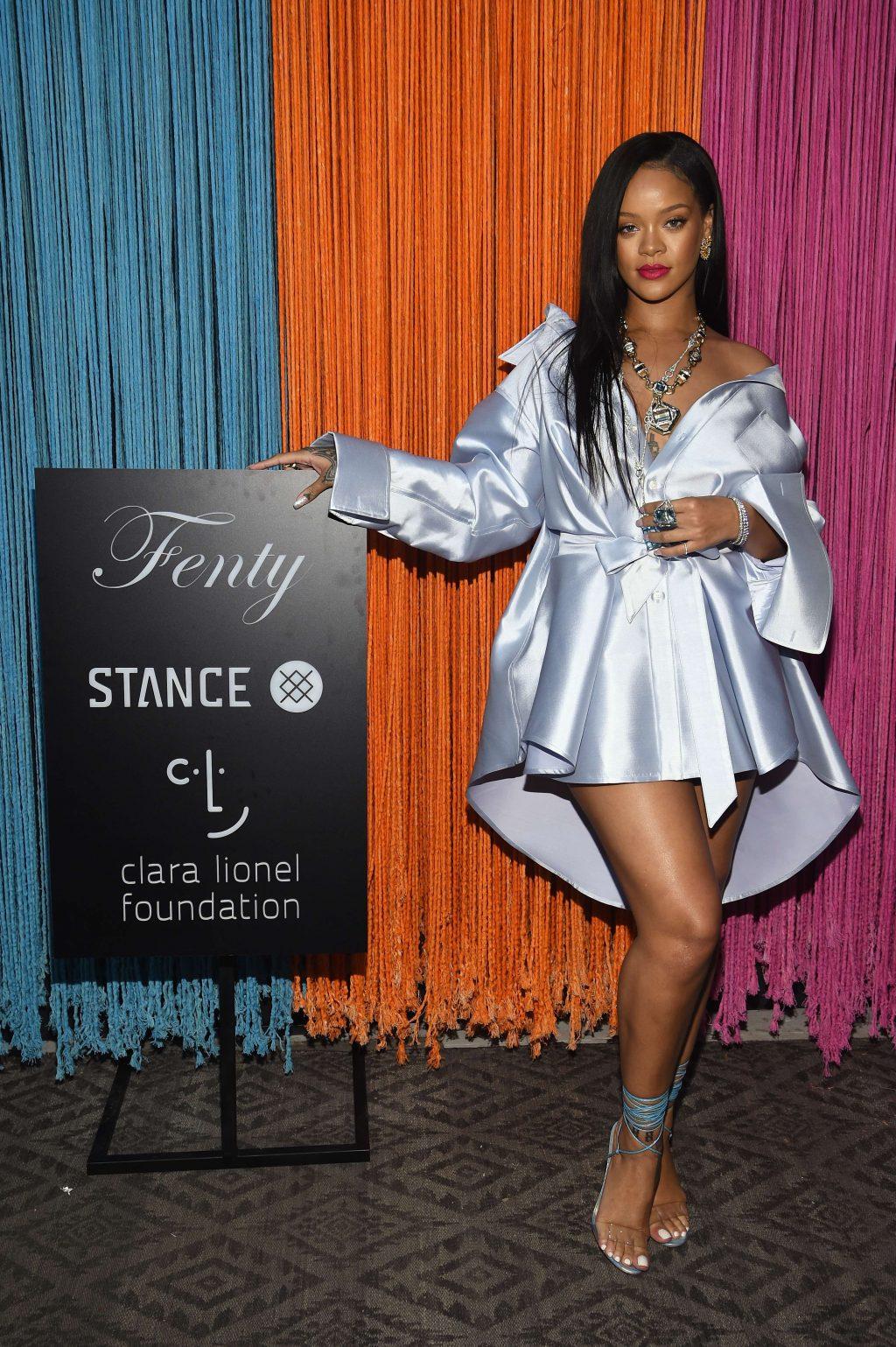 rihanna mặc áo trễ vai đứng cạnh booth Fenty