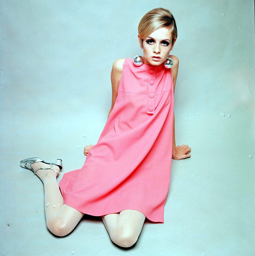 Gắn liền với thiết kế thời trang của Quant, Twiggy diện váy mini hồng cùng tất trắng, giày cao gót ánh kim và hoa tai đồng bộ