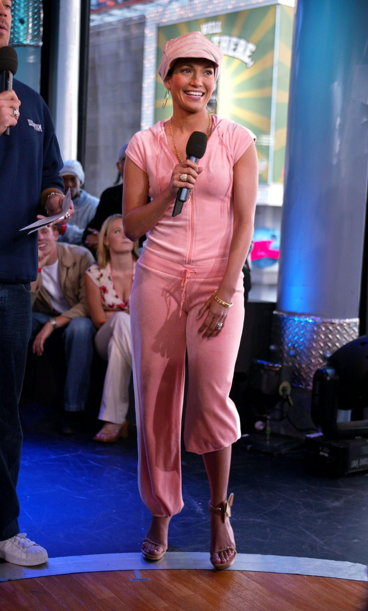 Jennifer Lopez mặc tracksuit hồng cùng mũ nồi và giày cao gót đồng bộ những năm 2000s