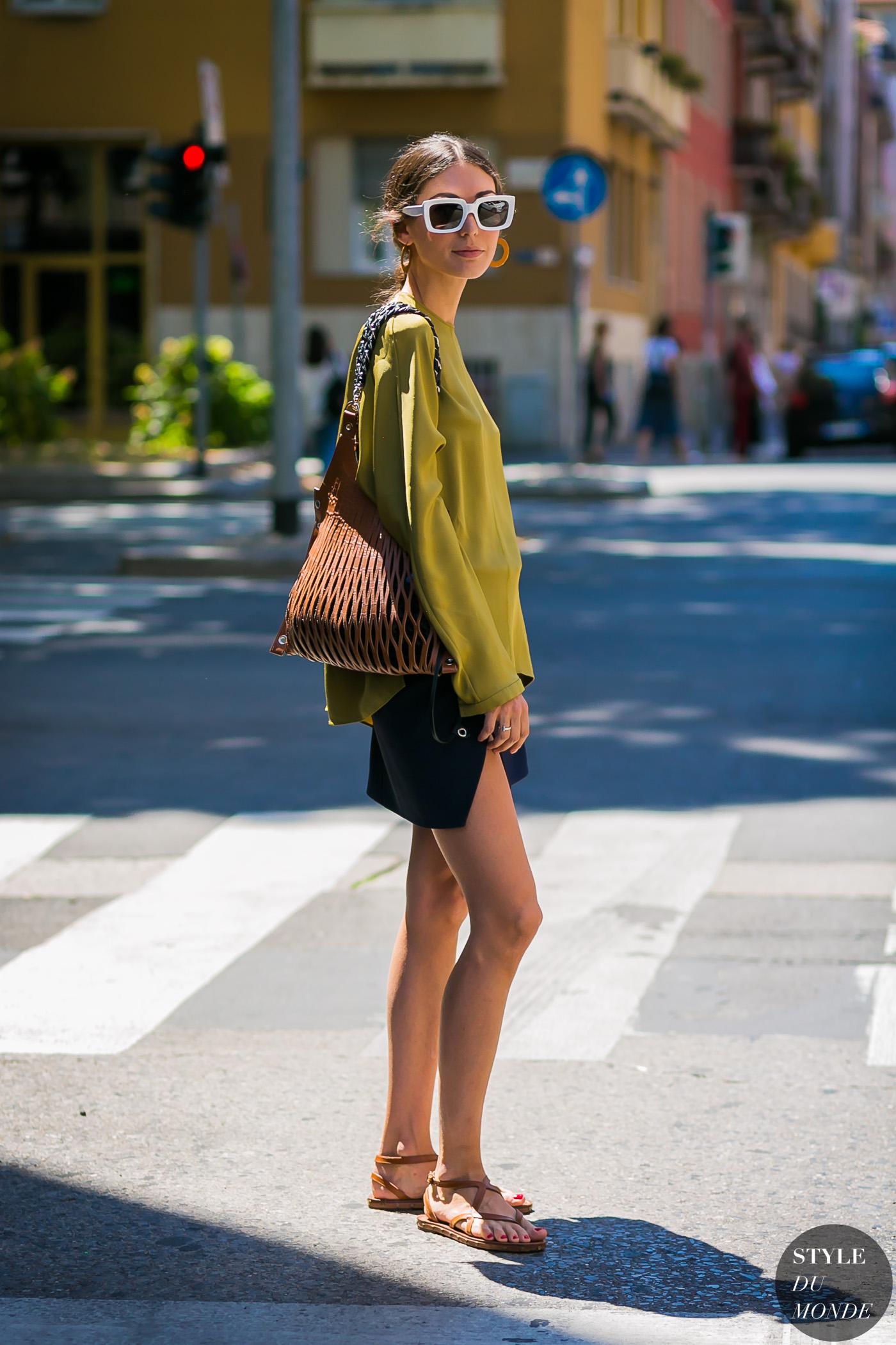 fashionista diện áo sweater vàng mustard cùng túi xách đan, sandal và kính mát bản to tại Tuần lễ Thời trang Milan dành cho nam Xuân - Hè 2018