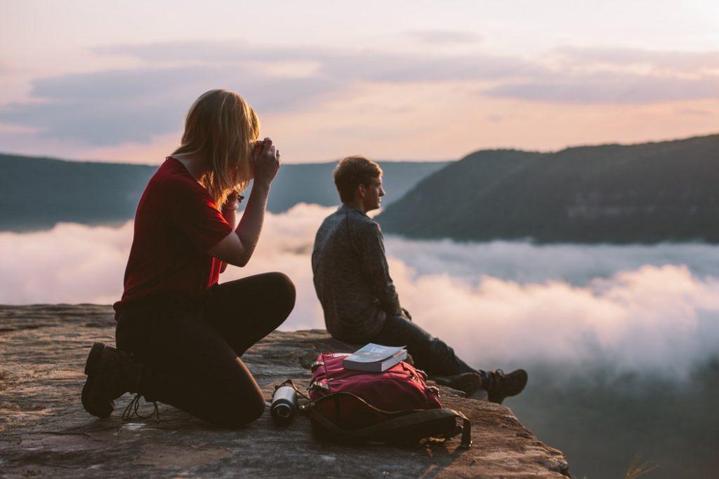 cô gái chụp ảnh cho chàng trai trên đỉnh núi đầy mây