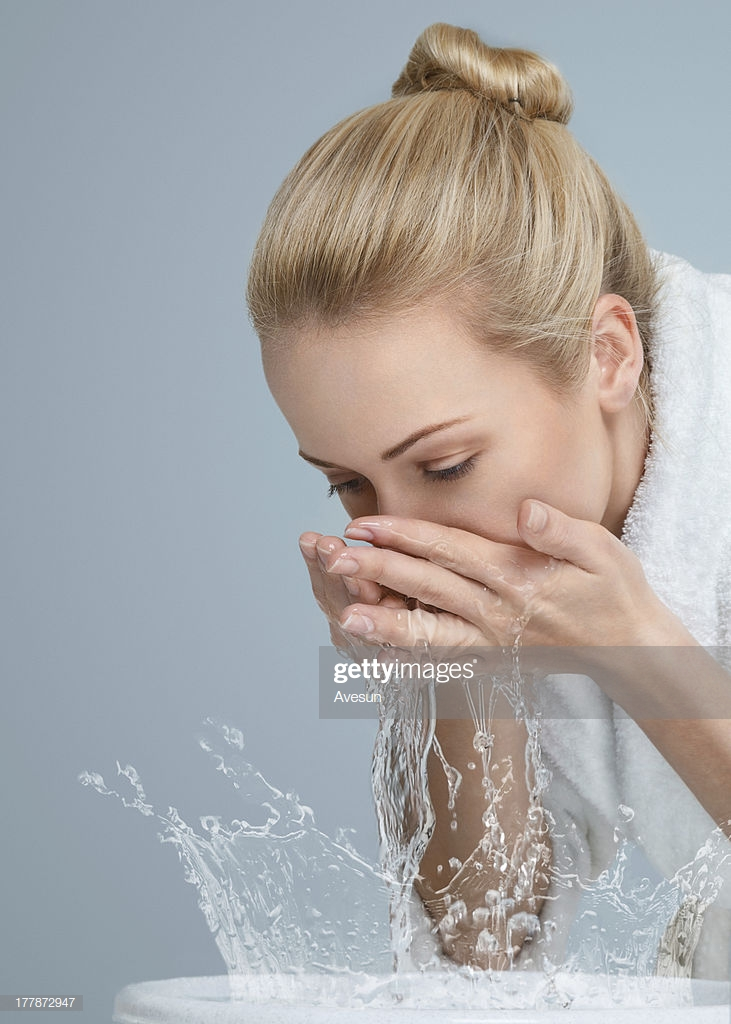 Cô gái đang rửa mặt với nước trong bồn rửa