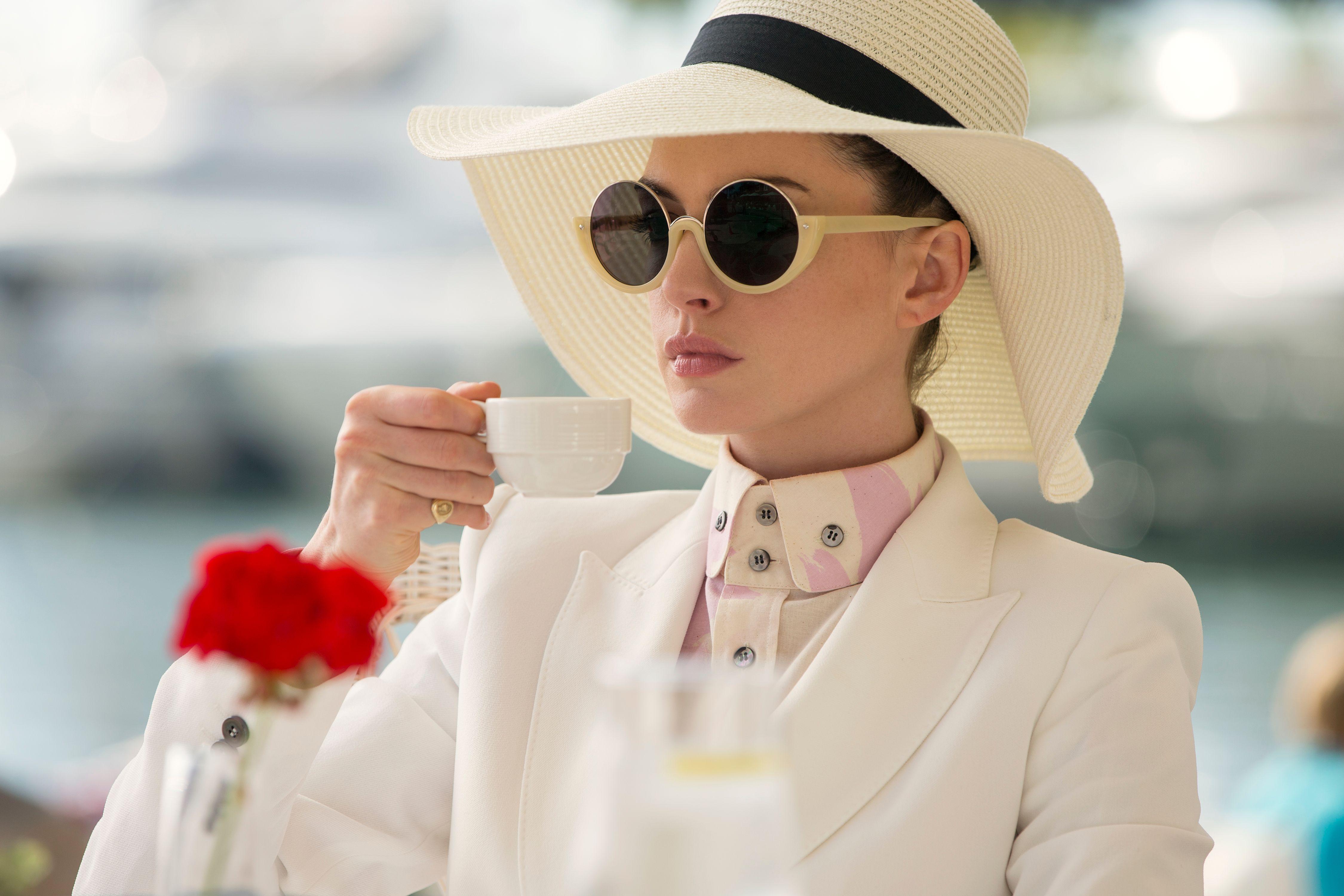 diễn viên Anne Hathaway diện âu phục trắng, sơmi cài cùng mũ rộng vành và kính mát đen gọng tròn