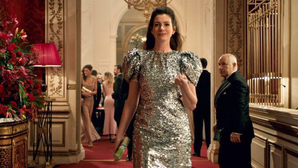 nữ diễn viên Anne Hathaway diện đầm metallic tay phồng và cột tóc trong Quý cô lừa đảo