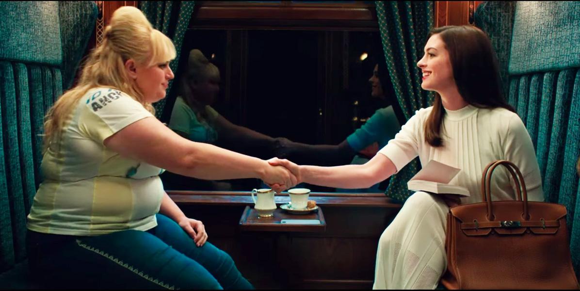 nữ diễn viên Anne Hathaway diện váy trắng tay lỡ trên chuyến tàu cùng Rebel Wilson trong The Hustle