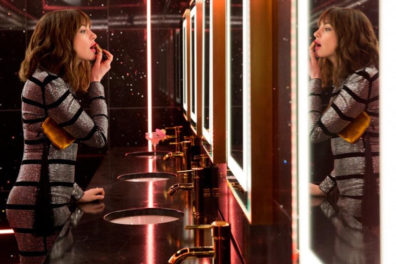 nữ diễn viên Anne Hathaway bôi son trước gương. Cô diện đầm bodycon ánh kim