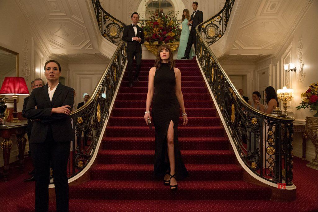nữ diễn viên Anne Hathaway bước xuống bậc thang trong bộ đầm cổ yếm đen xẻ tà và giày cao gót