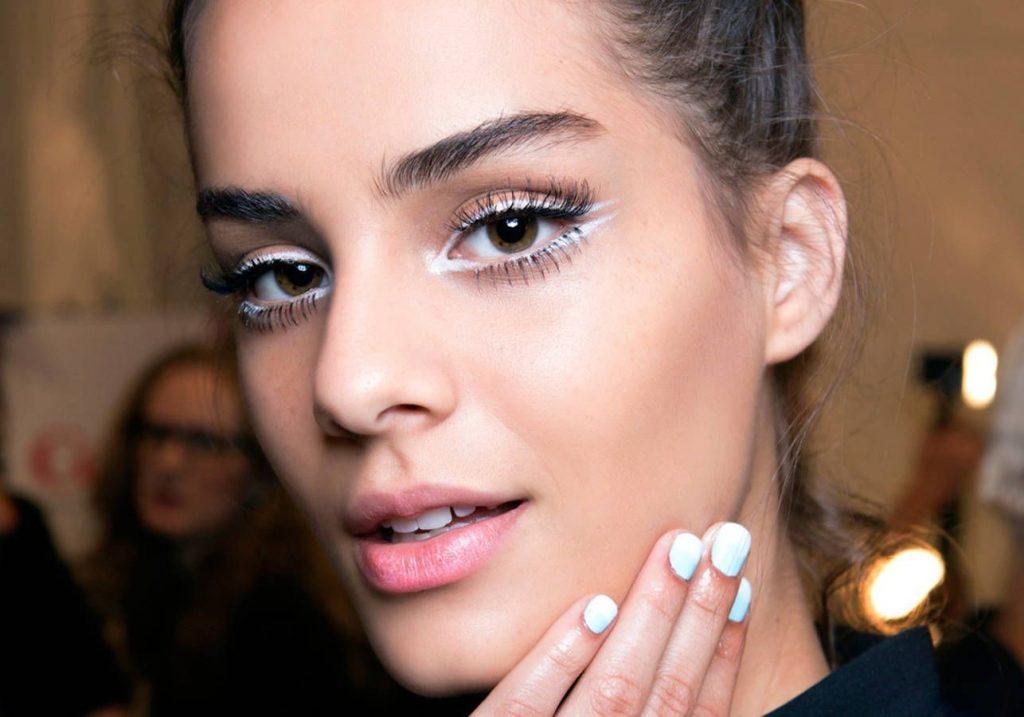 cô gái chạm tay lên mặt eyeliner màu trắng